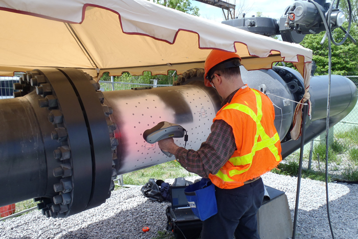 An engineer conducts 3D testing of a pipeline with a Creaform Handyscan3D scanner.
