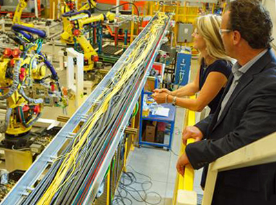 Carolyn Garvey and Don Leslie, CEOs of Prodomax, observe a production line.