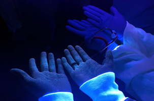 Tell-tale fluorescent liquid visible on healthcare workers' skin.