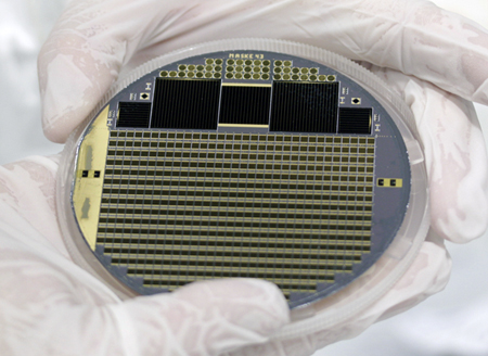 Solar cell wafer with four-junction concentrator cells and test structures.