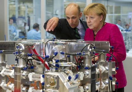 Peter Leibinger describes a laser resonator to Chancellor Merkel.