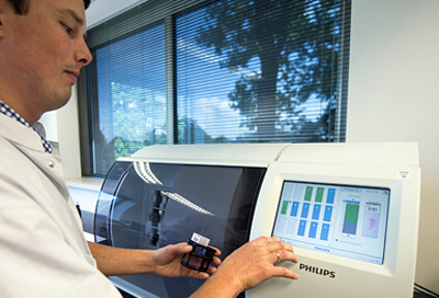 Quick turnaround: a technician inserts tissue slides into Philips IntelliSite ultra-fast scanner.