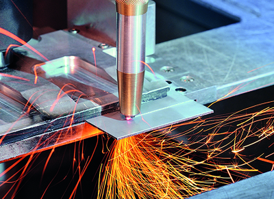 Laser cutting head with diamond optics has water cooling and shield gas supply.
