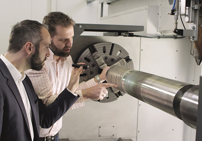Thomas Schopphoven and IHC's Andres Veldman inspect an EHLA-treated cylinder.