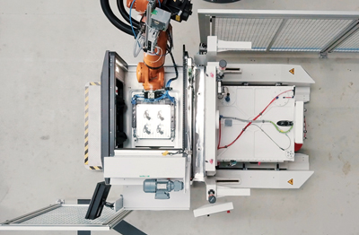 A robot removes the additively manufactured parts from the build platform.